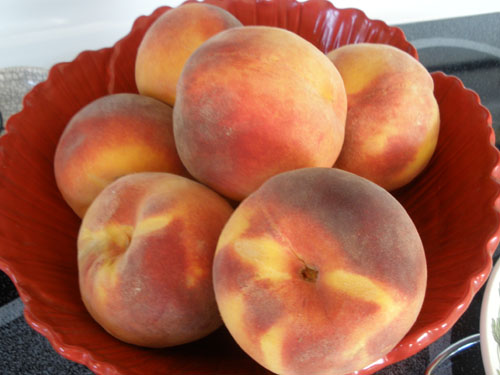 Ripe, Round Peaches in Red Bowl