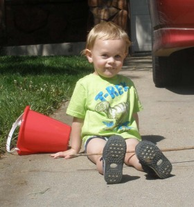 small boy sits in driveway with bucket