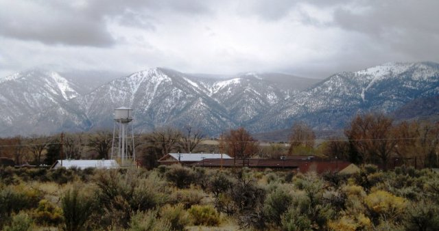 water tower in foreground with mountain peaks in background