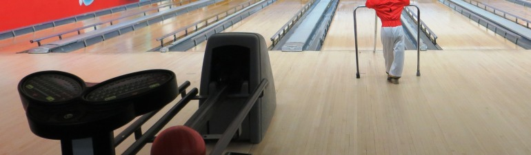 Little boy uses ramp to help him bowl.