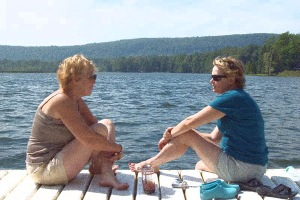 Women sitting on a dock, having an intimate conversation during friend therapy