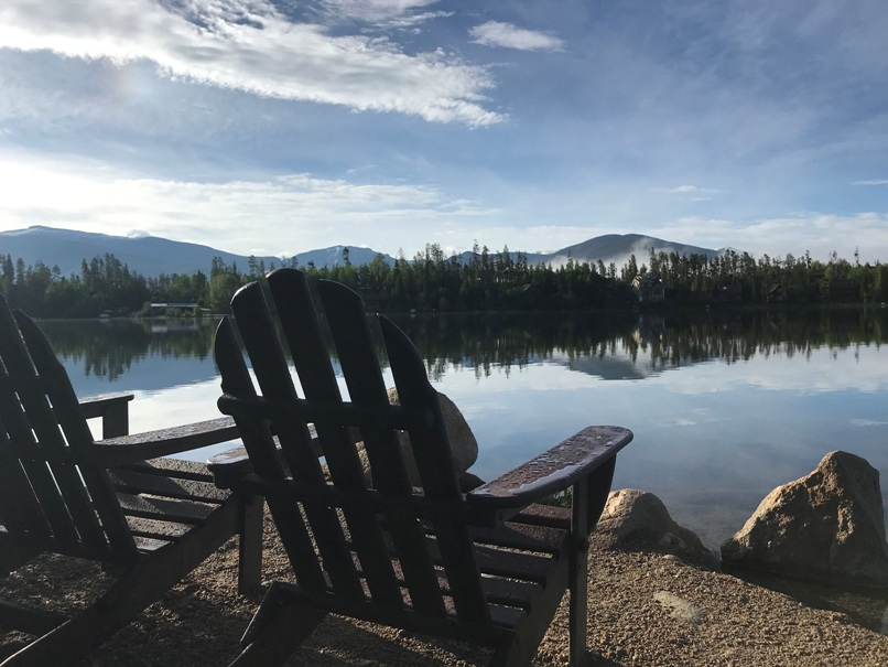 Happily after retirement , sitting in an Adirondack chair facing water early morning in Grand Lake, CO.